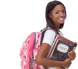 Smiling female college student carrying a backpack holding books