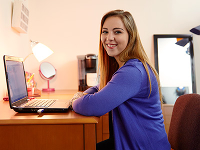 Photo of a student at a desk in a GBC dorm room