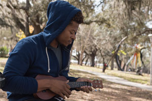 A student plays a ukelele on campus