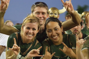 USF students at football game in green and gold paint.